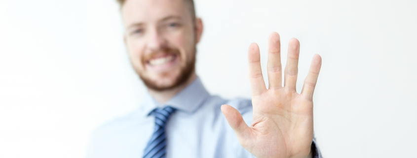 Close up of business man with five fingers held up